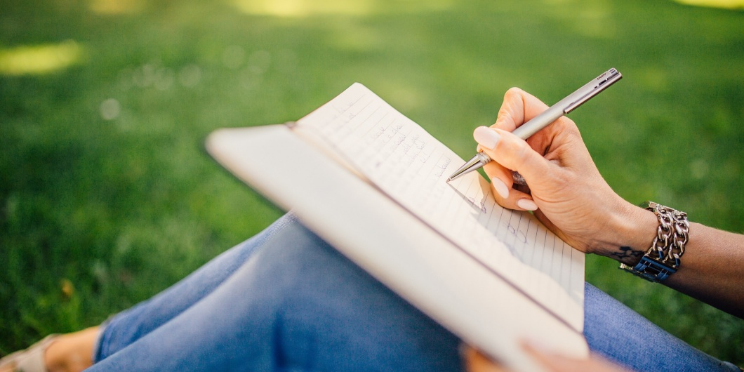 a woman writing in a journal overcoming procrastination christian