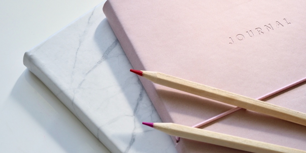 two journals one pink one marble