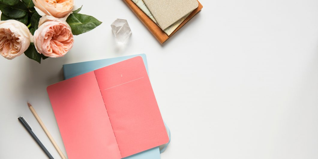 This is a picture of a peach journal and peach flowers on a white desk. This post is about Tailwind Tribes To Join