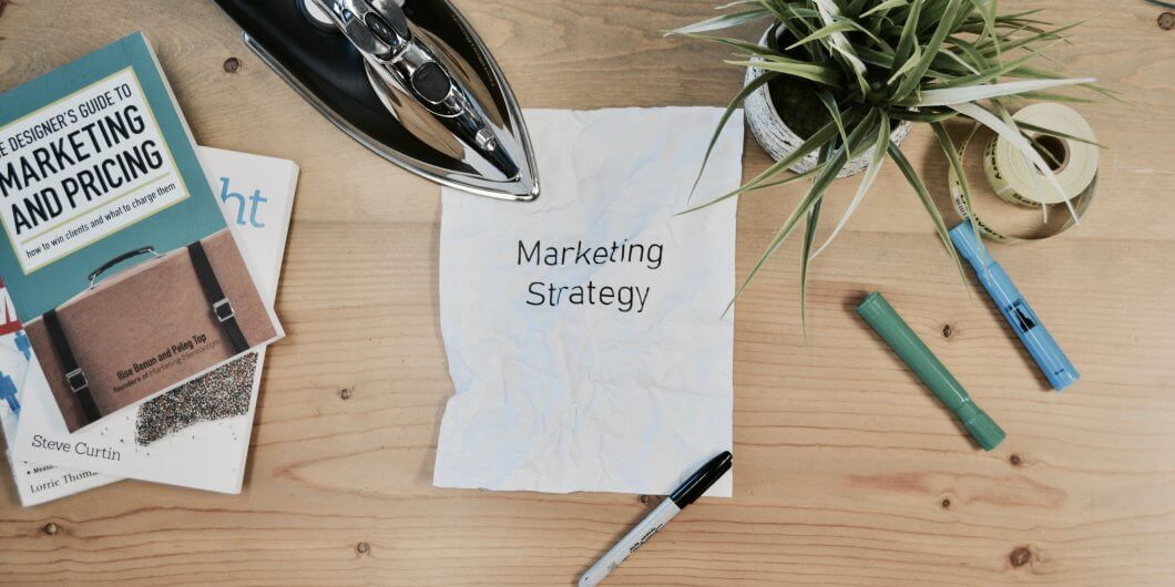white paper on a desk with marketing strategy written on it