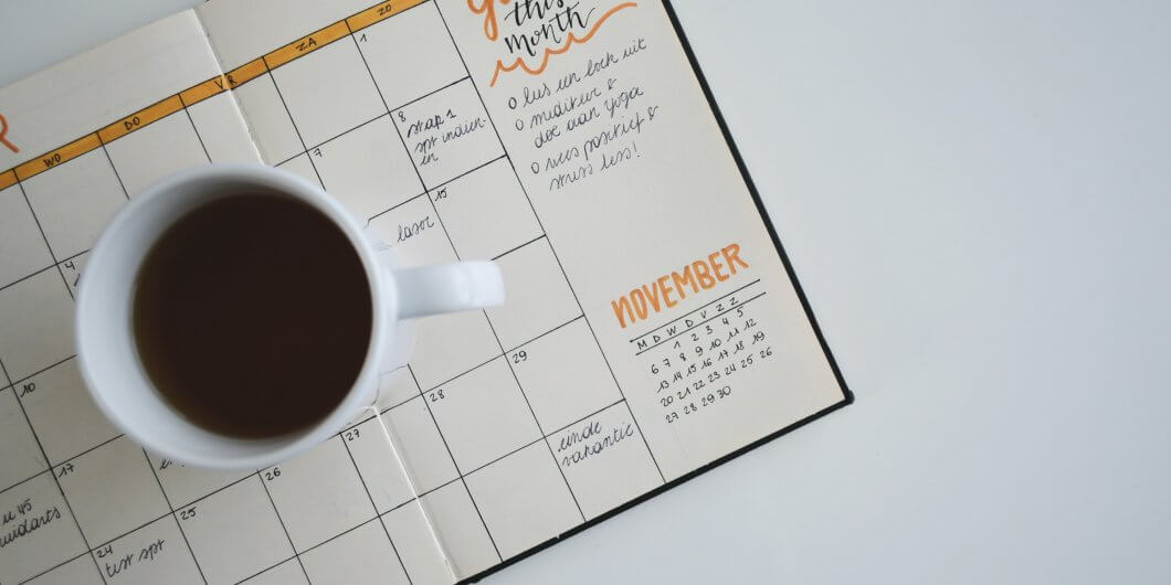 a blogging goals planner on a white desk with a cup of coffee on top